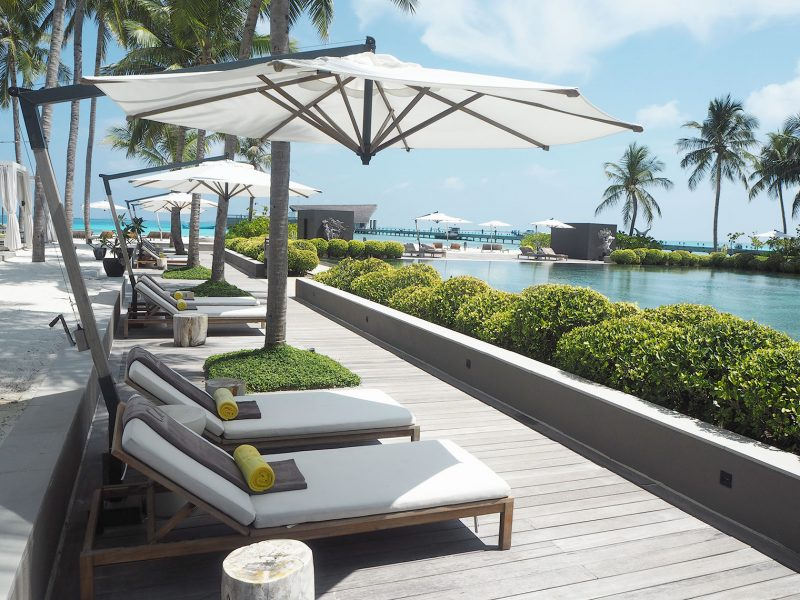 Sun lounges by the main swimming pool at Cheval Blanc Maldives