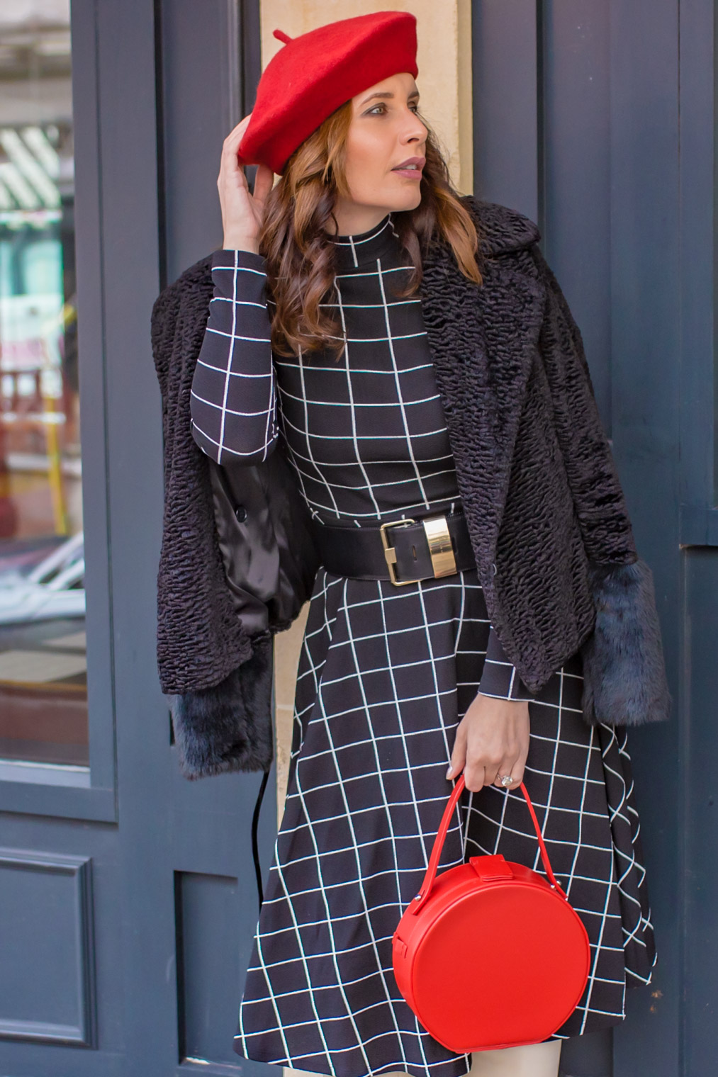 Black faux fur coat red bag and black dress with white checks